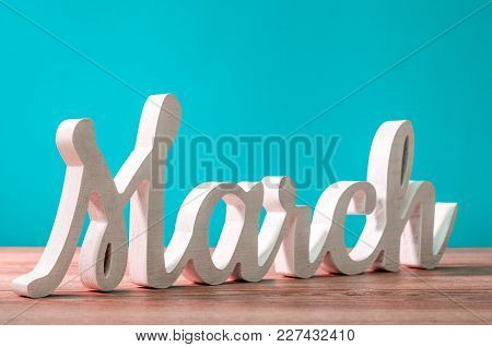 March - Wooden Carved Word At Turquoise Background. Beginning Of March Month. Spring Is Coming.