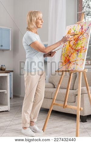 Time For Creating. Appealing Attractive Mature Woman Staying Near Easel While Painting And Posing In