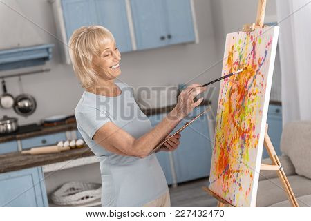 Talented Person. Pretty Cheerful Mature Woman Painting With Tassel While Smiling And Looking At Ease