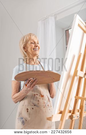 My Work. Low Angle Of Gay Joyful Mature Woman Admiring Her Painting While Grinning And Carrying Pale