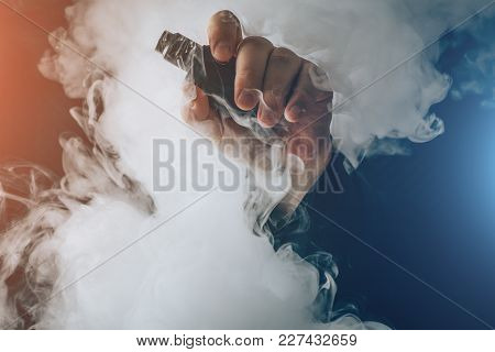 Man Hand Shows Vape Device At Cloud Of Vapor Background. Vape Concept, Toned