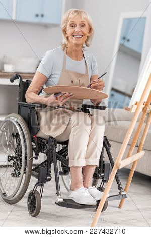 Happy Life. Disabled Mature Nice Woman Posing In Wheelchairs While Grinning And Carrying Pallet And