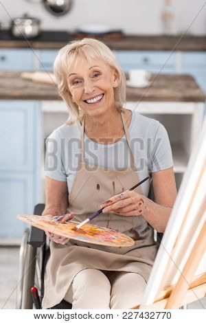 Be Free. Mature Handicapped Beautiful Woman Sitting In Wheelchair While Looking At Camera And Drawin
