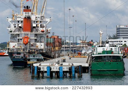 Labuan,malaysia-feb 2,2018:container Ship Docked In Port Of Labuan Port Background Of Labuan Town In