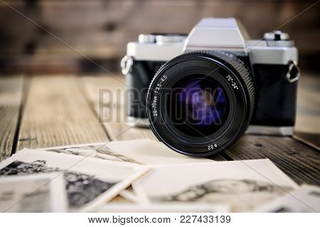 Close Up Of Vintage Photographic Prints, Film Camera And On A Rustic Wooden Table.