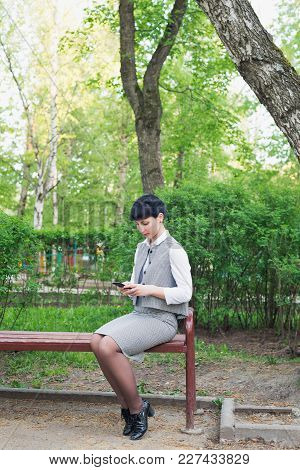 A White Caucasian Woman Is Sitting In Summer Business Clothing On Bench In Park