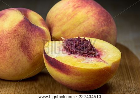 Fresh Nectarines On A Bamboo Cutting Board, With One Sliced In Half In Foreground, Showing The Pulp