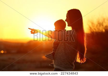 Backlight Silhouette Of A Mother Pointing Horizon With Her Baby At Sunset