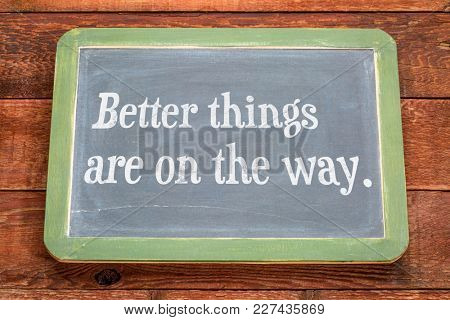 Better things are on the way. White chalk text on a vintage slate blackboard against rustic barn wood.