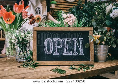 Wooden Table With Floral Arrangements And Blackboard Saying Open In Flower Shop.
