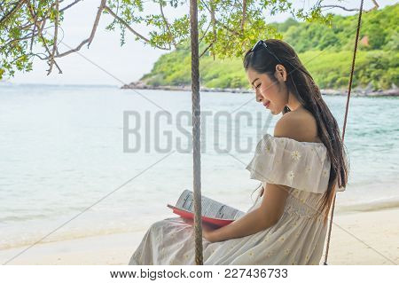 Traveler Woman Reading A Book Relaxing On Swing Her Feeling Freedom And Looking Destination Sea Beac