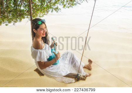Traveler Woman With Ukulele Relaxing On Swing Her Feeling Freedom And Looking Destination Sea Beach.