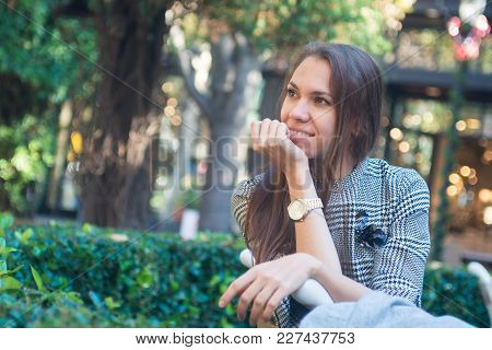 Stylish Young Happy Woman Sitting On The Bench Outside, Smiling, City Street With Storefronts On Bac