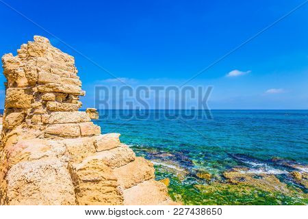 Flooded in the sea ruins and remains of ancient forts and fortifications. Ruins of the ancient city and port of Caesarea. Spring day in Israel. Concept of archeological and historical tourism