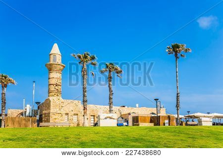 Israel. Sunny spring day. Ruins of the ancient city and port of Caesarea. The restored minaret of the times of the Arab invasion. Concept of archeological and historical tourism