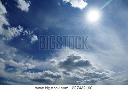 Natural bright sun on dark blue sky background.