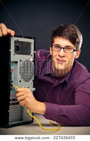 Young Computer Nerd Connecting A Network Cable