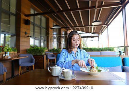 Gladden Female Customer Eating Dessert At Restaurant   With Satisfied Smile. Charming Girl Enjoying