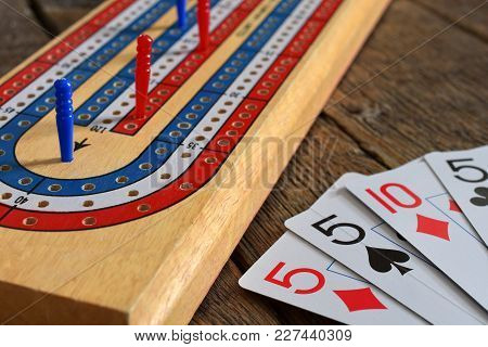A Close Up Image Of An Old Wooden Cribbage Board With Red And Blue Cribbage Pegs.
