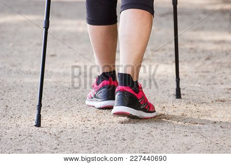 Legs Of Elderly Senior Woman In Sporty Shoes Practicing Nordic Walking, Concept Of Healthy Sporty Li