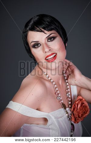Elegance, Brunette girl with short hair, French mane in the style of the 20s. She wears white fur coat and jewelry