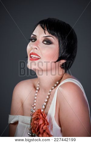 Luxury, Brunette girl with short hair, French mane in the style of the 20s. She wears white fur coat and jewelry
