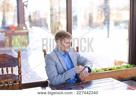Businessman Enjoying Smart Watch At Cafe With Tablet, Roll Project And Black Document Case On Table.