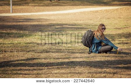 Young Tourist Woman Taking A Break From Hiking, Sitting On The Grass Before Moving Forward