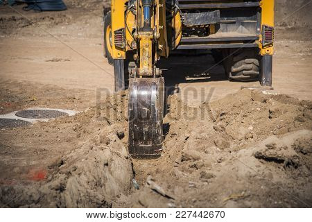 Yellow Digger, Excavator Or Bulldozer, Rebuilding Terrain Next To A Modern Building