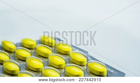 Macro Shot Detail Of Yellow Oval Tablet Pills In Blister Packs On White Background With Copy Space.
