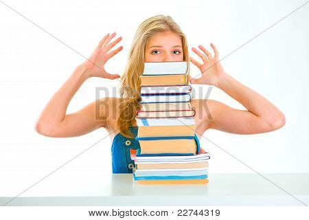 Sitting At Table Stressed Teen Girl Looking Out Of Pile Of Book