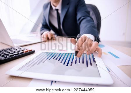 Man working at table in office, closeup. Financial trading concept