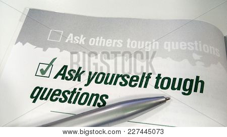 Ask Yourself Tough Question Printed On A Book