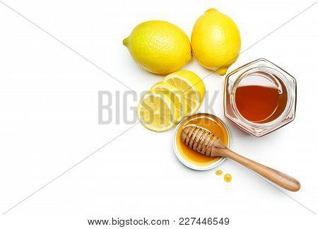 Honey Dipper And Fresh Lemon Over White Background