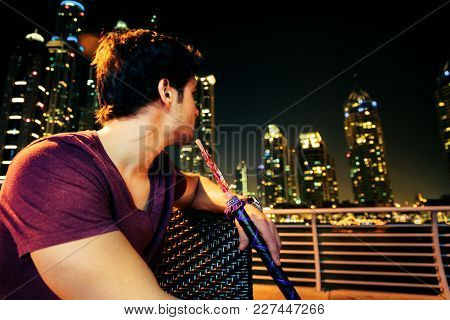 Young Man Sitting In A Cafe At Dubai Marina, Enjoying A Shisha