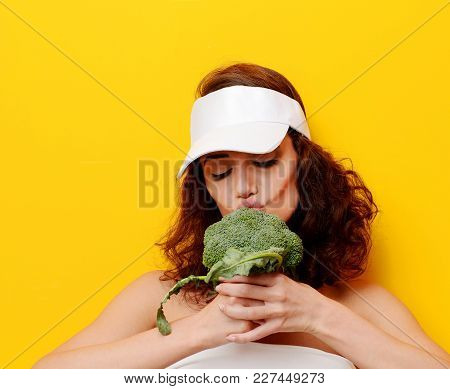 Young Woman Bite Big Fresh Green Broccoli Vegetable In White Hat. Diet Healthy Eating Concept Isolat