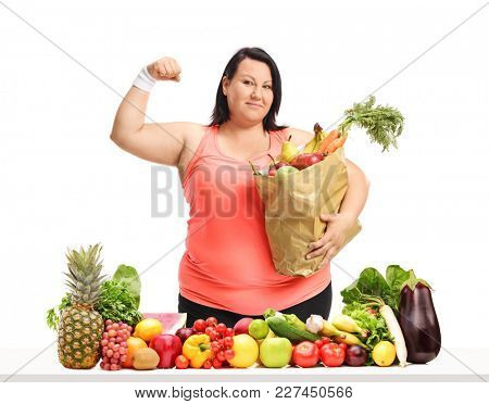 Overweight woman with a paper bag flexing her biceps behind a table with fruit and vegetables isolated on white background