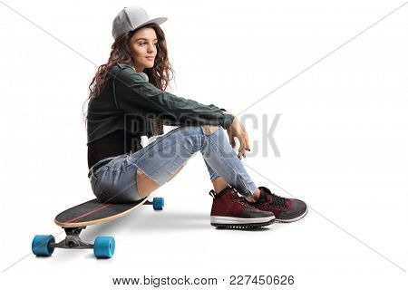 Teenage skater girl sitting on a longboard isolated on white background