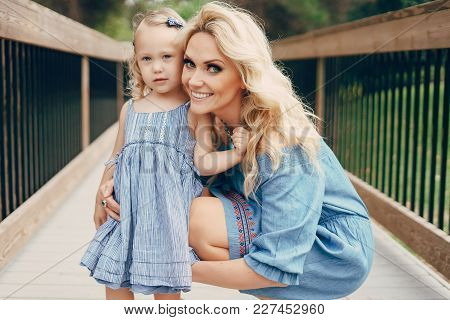 Young Beautiful Mother With Blonde Little Girl Walking In The Park