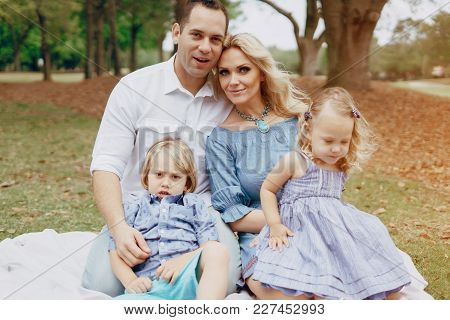 Beautiful And Happy Young Family Mom Dad Son And Daughter Blonde Walking In The Park Near Their Home