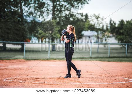A Teenage Girl Holding Glove Up To Her Face With Long Hair In A Ponytail Standing On The Pitchers Mo