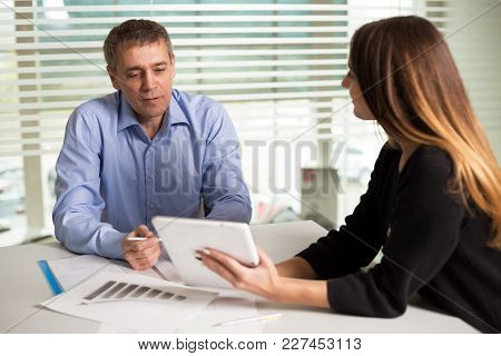 Man And Woman Working In Bright Office Classic Suits And Talk, Solve The Issues Of The Company
