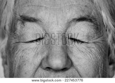 Black and white portrait of a white elderly woman eyes closed