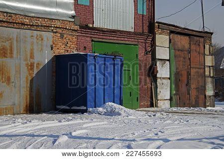 Garage doors. Colored metal doors. Garages. Old garages. Blue container. Green door.