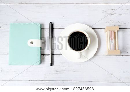 Top View And Selective Focus Of A Cup Of Black Coffee With Hourglass, Notebook And Pen On White Wood