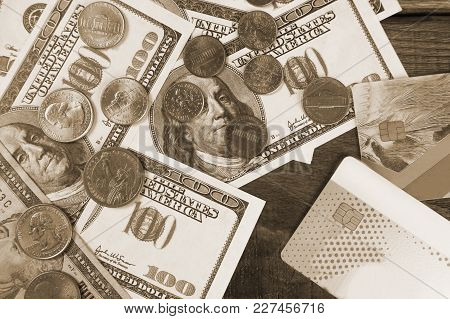 Hundred Dollar Bills And One Dollar Coins On A Wooden Background. Copy Paste