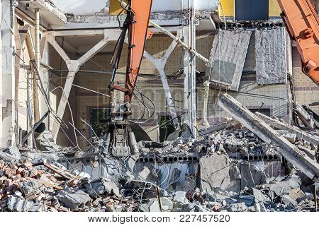 Building Demolition. Excavator Removes Pieces Of Metal And Stone From Demolition.