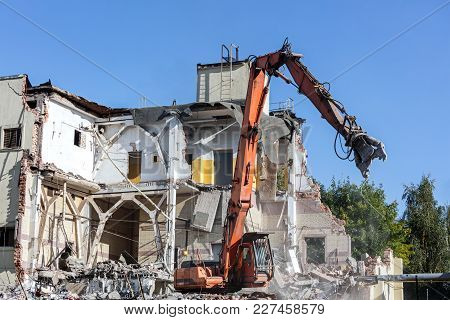 Excavator With Hydraulic Shears On Construction Site. Dismantling Building.