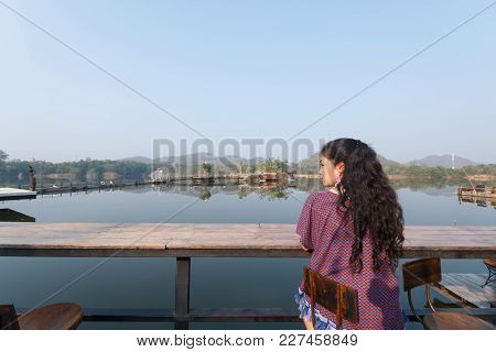 Beauty Asian Woman Sitting At Chair And Beautiful Natural View On Background, Relax And Vacatio Conc