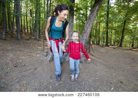 Mother And Child Laughing In Forest Of Chestnut Trees
